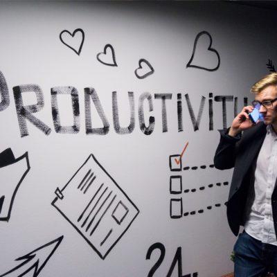 """Homme un téléphone à la main, devant un tableau sur le quel il est marqué """"productivité"""". Il s'agit d'un évènement professionnels"""